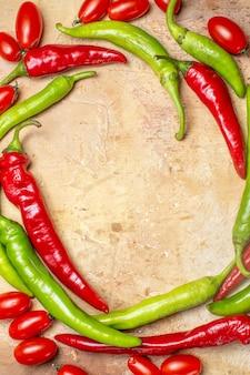 호박색 표면에 있는 상위 뷰 원 모양의 고추와 체리 토마토