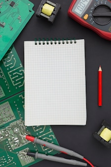 Top view circuit board with a blank notepad