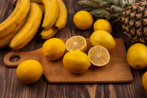 Top view of citrus fruit half and whole lemons on a wooden kitchen board with pineapple and bananas isolated on a wooden surface
