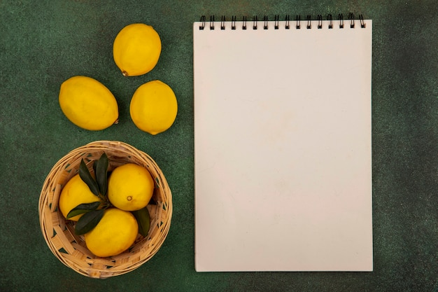 Vista dall'alto di limoni di agrumi su un secchio con limoni isolato su una superficie verde con spazio di copia