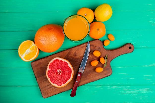 Vista dall'alto di agrumi come pompelmo kumquat con coltello sul tagliere e arancio mandarino limone con succo d'arancia su sfondo verde