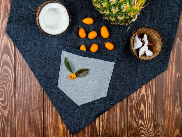 Top view of citrus fruits as half cut coconut with coconut slices in shell kumquats pineapple on jeans cloth and wooden background