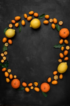 Top view of citrus fruits as kumquats lemons and tangerines set in a circular manner on black surface