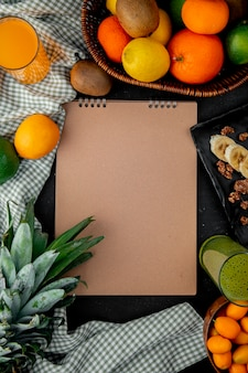 Top view of citrus fruits as orange kiwi pineapple on cloth surface with copy space