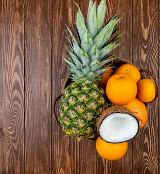 Top view of citrus fruits as pineapple coconut orange tangerine in basket on wooden background with copy space