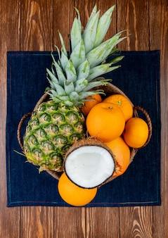 Vista superiore degli agrumi come merce nel carrello arancio del mandarino della noce di cocco dell'ananas sul panno dei jeans e sul fondo di legno