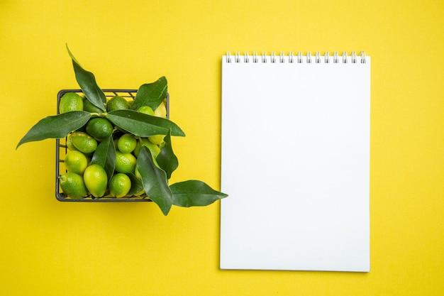 葉の白いノートと緑の柑橘系の果物の上面図柑橘系の果物のバスケット