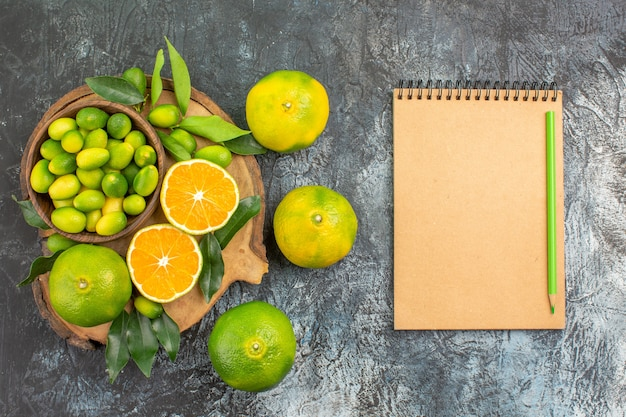 Top view citrus fruits the board with different kinds of citrus fruits notebook pencil