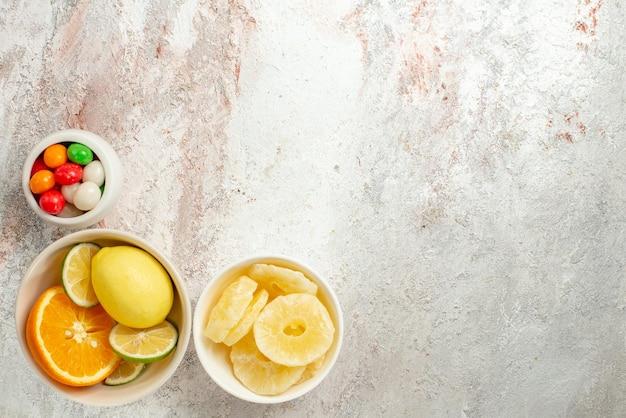 테이블 왼쪽에 있는 다채로운 사탕 말린 파인애플과 감귤류 과일의 상위 뷰 감귤류 그릇