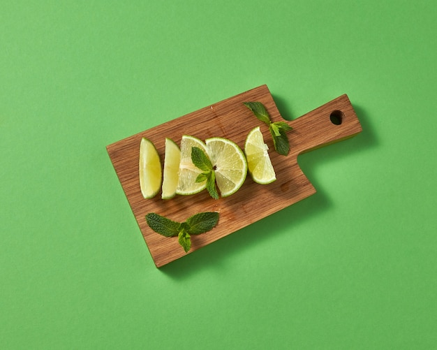 Top view of citrus fruits green lime with sprigs of green mint on brown board on a green wall. concept of cold alcoholic or non-alcoholic summer drinks.