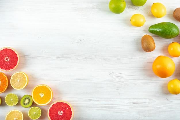 Top view citrus fruits kiwi green and yellow lemon grapefruit orange with copy space