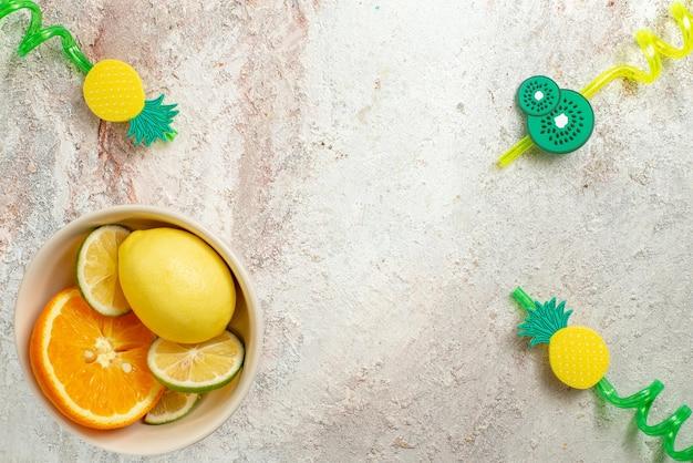 Вид сверху цитрусовых, лимона, лайма и апельсина в белой миске с левой стороны стола