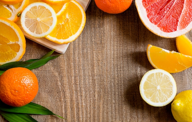 Top view of citrus fruits oranges, grapefruit, lemon, tangerines on wooden background