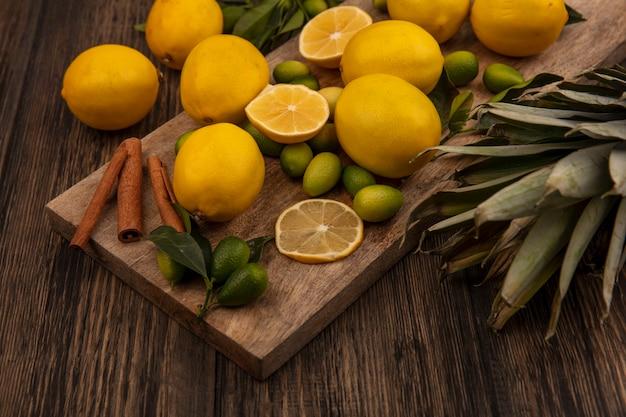 Vista dall'alto di agrumi come kinkan e limoni con bastoncini di cannella su una tavola da cucina in legno con ananas su uno sfondo di legno