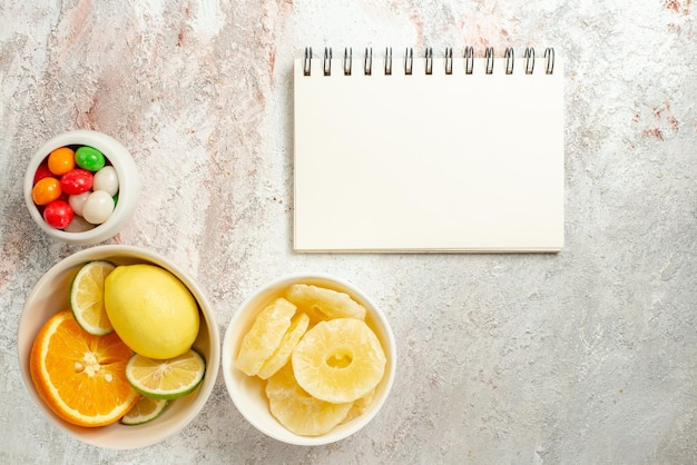 Top view citrus fruits white notebook next to the bowls of colorful candies dried pineapples and citrus fruits on the table