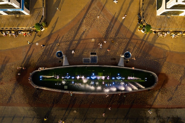 Top view of the city fountain in the new district of minsk mayak hot summer and vacationing people.people relax and walk near a large fountain in the city.belarus