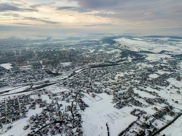 Top view of city suburbs or small town nice houses on winter morning on cloudy sky background. aerial drone photography concept.