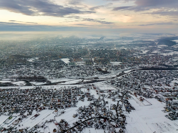 Top view of city suburbs or small town nice houses on winter morning on cloudy sky background