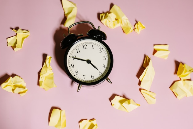 Top view of classic alarm clock with crumpled yellow sticky notes on pink background