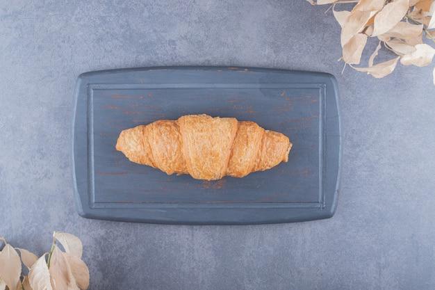 Vista dall'alto del classico croissant francese sul bordo di legno grigio