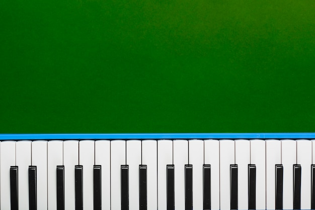 Top view of classical piano black and white keyboard on green background