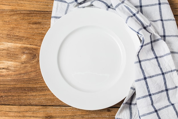 Top view of clean empty plate on wooden tabletop with napkin
