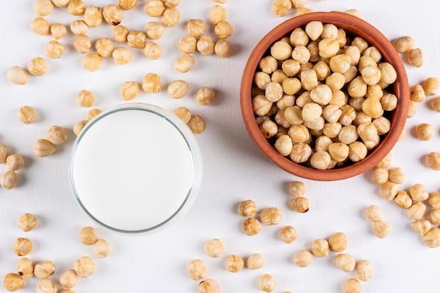 Вид сверху очищенного фундука со стаканом молока