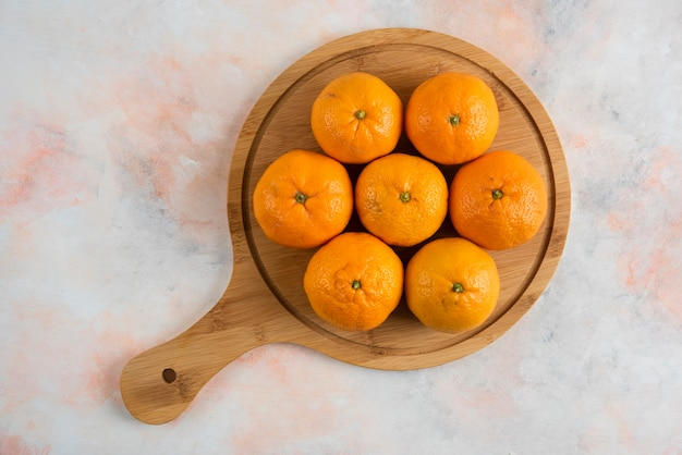 Top view of clementine mandarins on wooden cutting board over colorful surface
