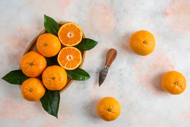 Top view of clementine mandarins over wooden plate
