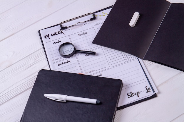 Top view clipboard with glass magnifier and copybook. white desk background.