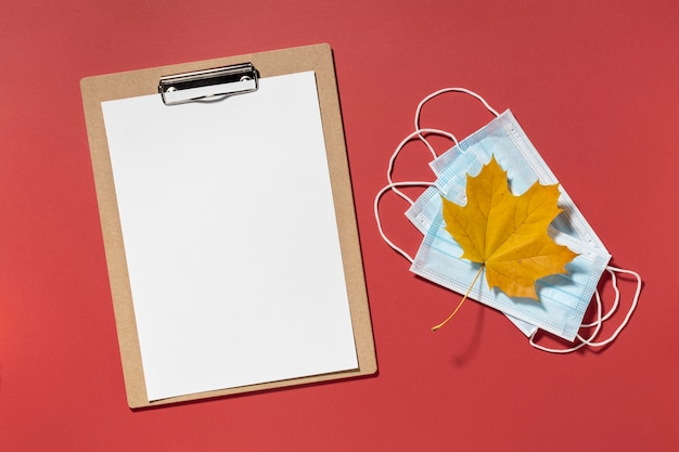 Top view of clipboard with medical masks and autumn leaf