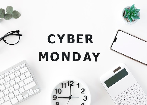 Top view of clock with smartphone and keyboard for cyber monday