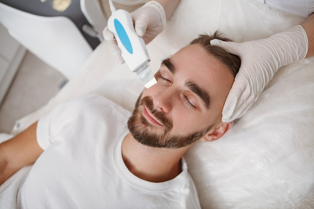Top view close up of a bearded man getting facial ultrasound cleanse at cosmetology salon