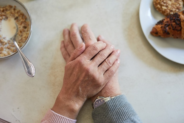 Top view close up of caring senior couple holding hands at dinner table copy space