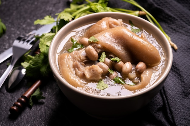 Top view, close up, copy space, taiwan asian distinctive street food, peanut pork knuckle soup in a beige ivory creamy-white colored bowl isolated on dark shale slate table