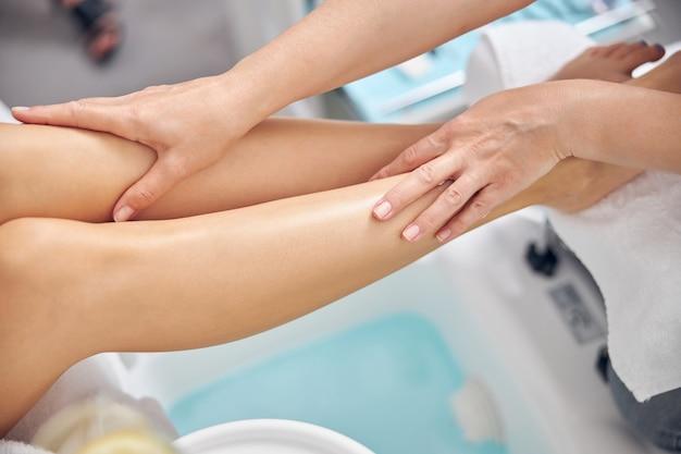 上面図は、リラクゼーションのために専門家によって扱われている女性の足のトリミングされた頭をクローズアップ