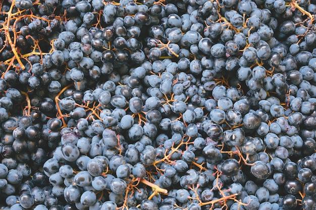 上面図は、自然食品の背景の暗いブドウの果実のテクスチャをクローズアップ
