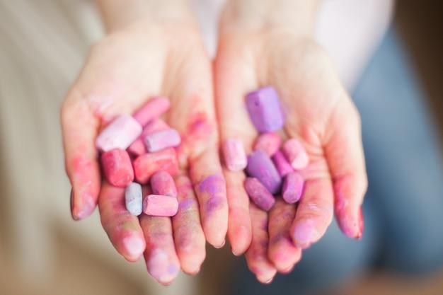 Вид сверху крупным планом женские руки, размытые фиолетовой краской, удерживают и тарелку с сухой пастелью теплых оттенков розового сиреневого и фиолетового. концепция творческой работы студии