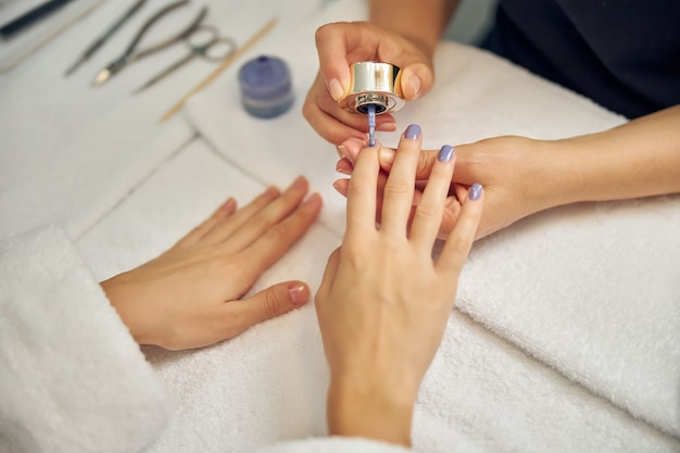 Top view close up of female hands at table while artist is applying nail polish