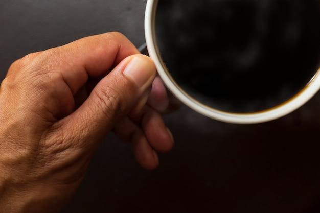 平面図は手マンがコーヒーカップを保持するを閉じます。コーヒーカップのブラックコーヒー。