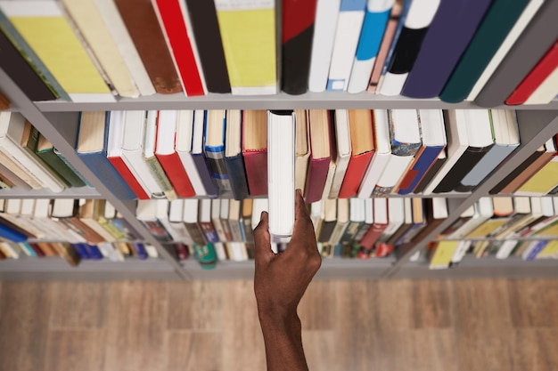 Top view close up of male hand taking book off shelf in library copy space