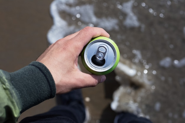 Top view, close-up of man holding a can of soda on the beach.