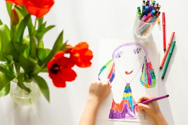 Вид сверху . крупным планом детские руки рисуем портрет мамы