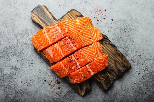 위쪽 전망, 나무 판자에 조미료를 넣은 신선한 생 연어 필렛 조각, 회색 돌 배경의 클로즈업. 요리를 위한 연어 필레 준비, 건강한 식생활 개념