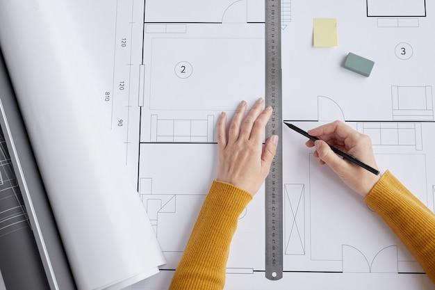상위 뷰는 사무실에서 책상에 앉아있는 동안 청사진과 계획을 그리는 여성 건축가의 닫습니다,