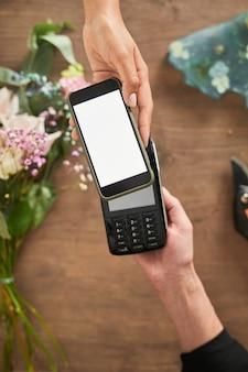 꽃가게 카피 공간에서 스마트폰으로 결제하는 여성 고객의 상위 뷰