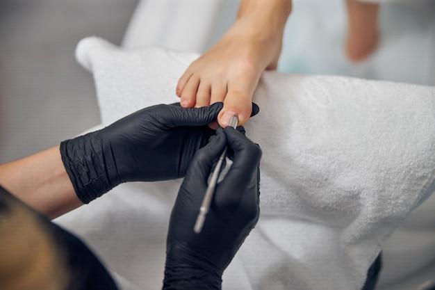 Вид сверху крупным планом женских ног, как художник id делает педикюр с толкателем для кутикулы