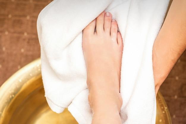 상위 뷰는 스파 뷰티 살롱에서 씻은 후 수건으로 백인 여자의 다리를 건조하는 남성 치료사의 닫습니다