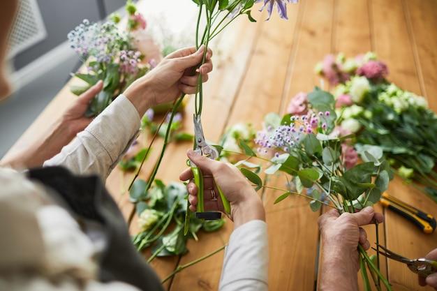 Вид сверху на двух флористов-женщин, создающих цветочные композиции в уютной мастерской