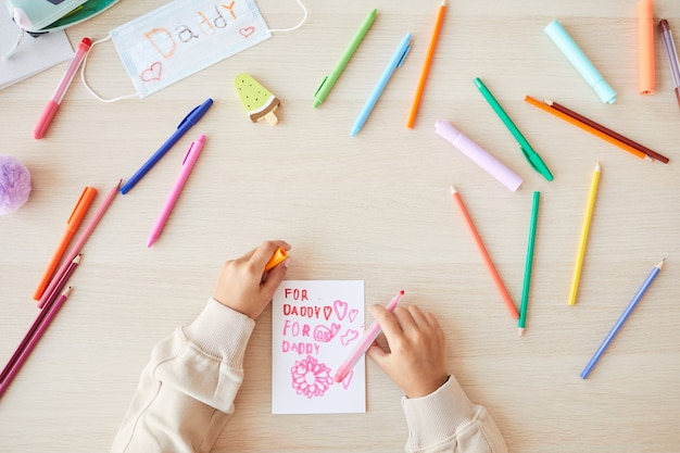 Вид сверху неузнаваемого ребенка смешанной расы, делающего открытку ручной работы в качестве подарка на день отца, копия пространства